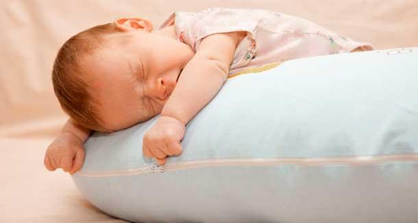 новорожденный ребенок спит на подушке